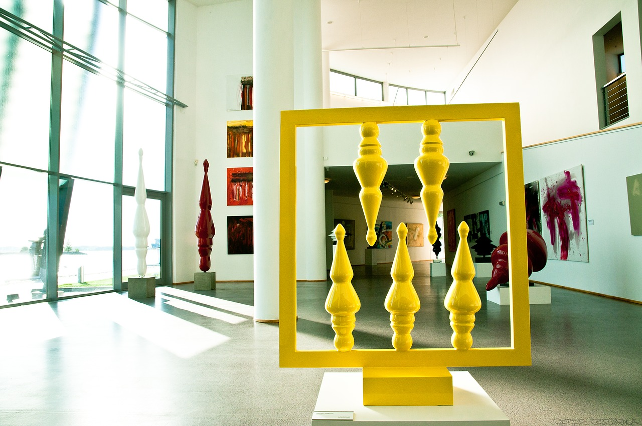 Interior of an art museum with thin yellow and red sculptures.
