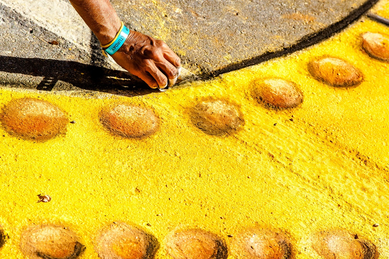 Person drawing with yellow sidewalk chalk.